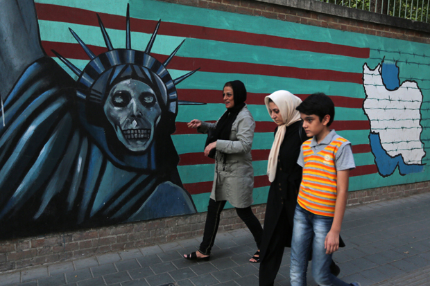 "An Iranian family walks past anti-US graffiti on the wall of the former US embassy in Tehran on July 14, 2015. President Hassan Rouhani told Iranians that ""all our objectives"" have been met by a nuclear deal agreed Tuesday after epic talks with world powers. Slogan in Farsi reads, ""Death to America"". AFP PHOTO / ATTA KENARE        (Photo credit should read ATTA KENARE/AFP/Getty Images)"