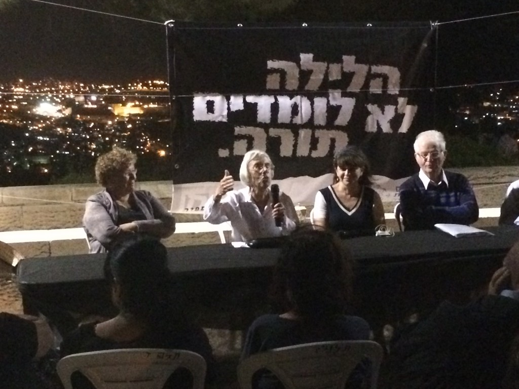 Panel discussion on national unity on Tisha b'Av with the Old City of Jerusalem in the background