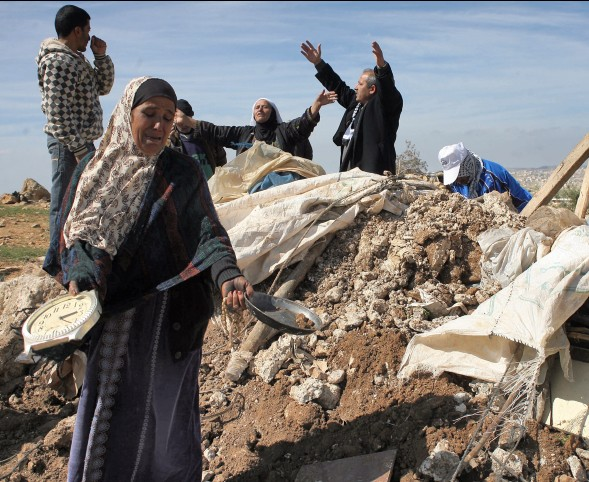 Palestinians try to retrieve items from the rubble of his family house after it was destroyed by Israeli army tractors early on 22 February 2011 in the West Bank village of Yatta near Hebron. The house was located in the so-called Area C, a closed military zone where Israel exercises full control and was built without permission, according to the Israeli army.Photo by Najeh Hashlamoun Flash 90