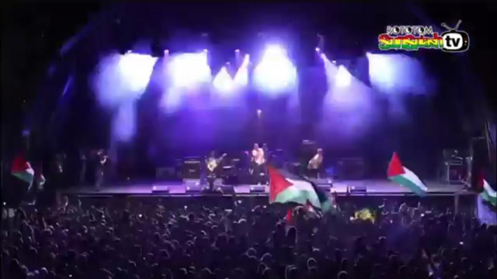 Matisyahy canta em show na Espanha frente a inúmeras bandeiras palestinas.