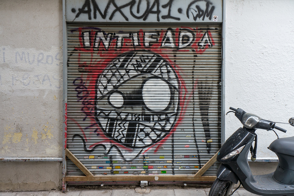 A Madrid garage door painted with a kaffiyeh-wrapped face and the word 'INTIFADA'.