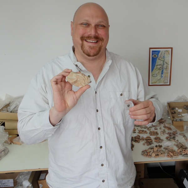 Nehemia Gordon holding an ancient Hebrew seal impression from the First Temple in his left hand and an actual piece of the Second Temple in his right hand.