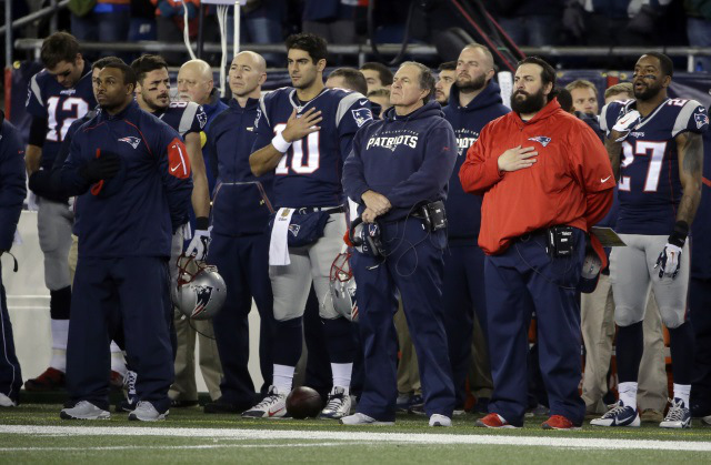 Patriots quarterback, Tom Brady (#12, far left), and coach Bill Belichick (center, blue) during the moment of silence