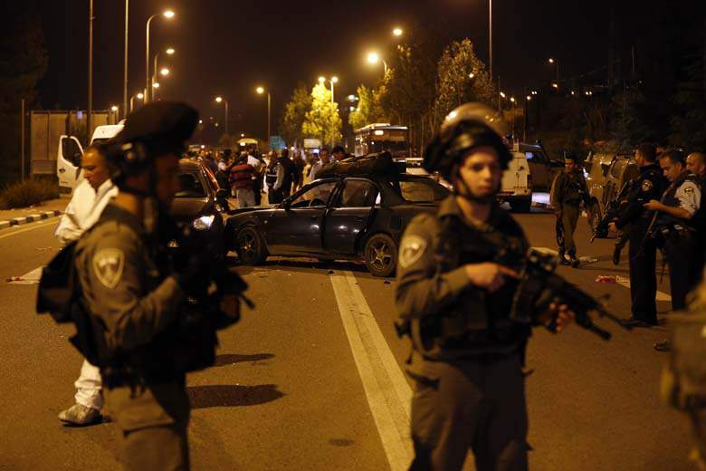 Israeli Defense Forces stand guard at the site of a terror attack at the Gush Junction. The attack left three dead, including 18 year old Ezra Schwartz (Image courtesy: ww.Heavy.com).