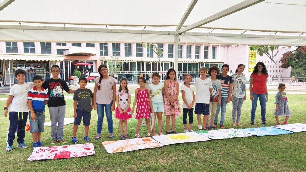 ACHLA students stand together with their joint art projects.