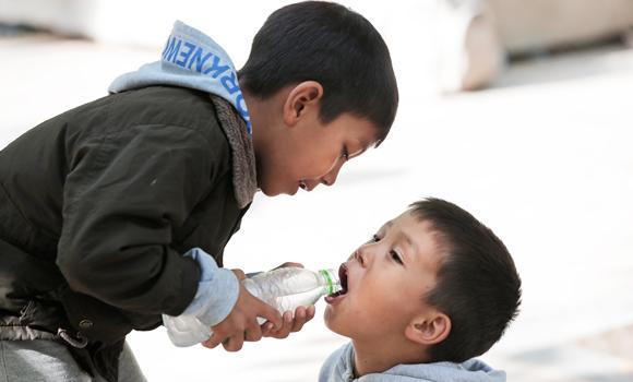 Migrant children sharing water