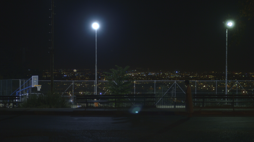 """A scene from """"Babies"""" at Har-Gilo, with the lights of Jerusalem in the distance."""