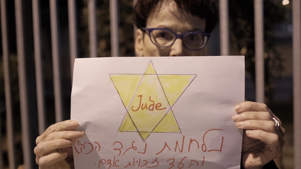 """Peace-Now activists hold signs reading """"the right wing will not silence us"""", as they protest an NGO bill proposed by Justice Minister Ayelet Shaked, her residence in Tel Aviv on December 26, 2015. Photo by Tomer Neuberg/FLASH90"""