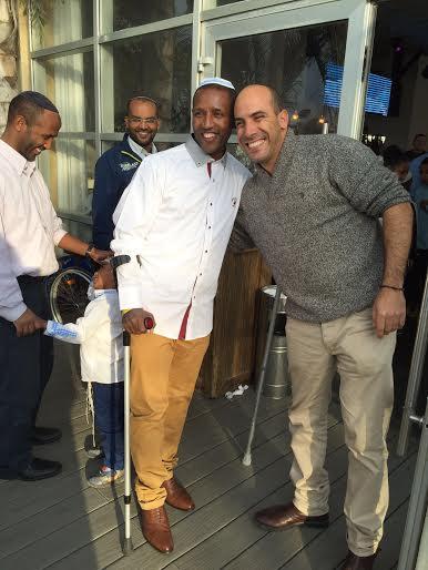 Awakke, left, standing despite the pain, during his son's brit with Tel Hashomer volunteer.