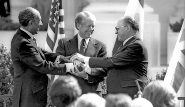 Sadat, Carter, and Begin signing the Camp David Accords (c. 1979). (Credit: Photo by Government Press Office)