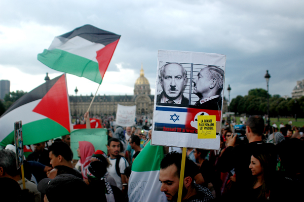 Protesters wave Palestinian flags and hold placards during a pro-Palestinian demonstration.