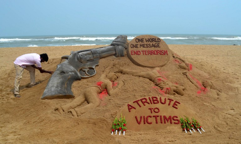 Indian sand artist Sudarsan Pattnaik puts the finishing touches to a sand sculpture at Puri Beach some 65kms east of Bhubaneswar on June 13, 2016, following an attack on a gay nightclub in the US city of Orlando. Law enforcement authorities have lowered the death toll from the weekend massacre at a gay nightclub in Orlando to 49, the deadliest mass shooting in American history, explaining that the shooter had been counted in the original tally. / AFP PHOTO / ASIT KUMAR