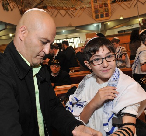 Boy putting on tefillin at the Bar Mitzvah Celebration