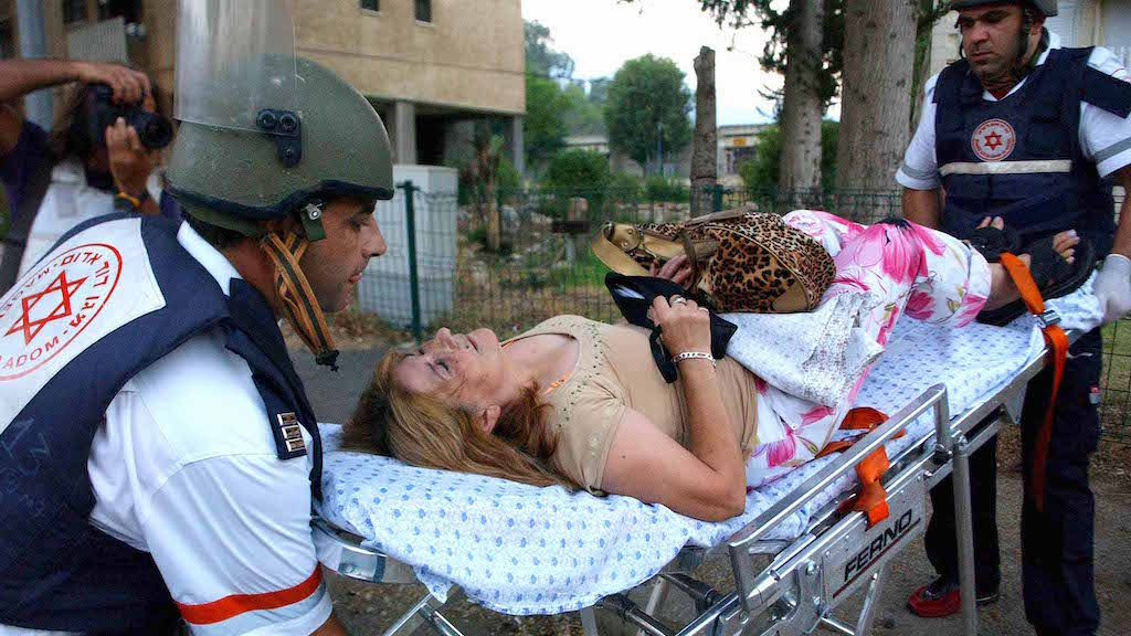 Israeli medics evacuate a woman in shock from her home after a rocket attack in the northern Israeli town of Kiryat Shmona Thursday July 27, 2006. Hezbollah has fired more than 1,400 rockets into Israel during the 16-days Israeli offensive in Lebanon, including 48 on Thursday. Photo by Flash90. *** Local Caption *** ÓÏÁÓ˙ Ï·ÂÔ ‰˘Èȉ ÚÂ¯Û ˜¯È˙ ˘ÓÂ‰ ÙˆÂÚ ÙˆÈÚ‰ ‡ÏÂ˜‰ ˜ËÈ¢‰ ʘ