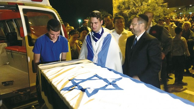 ome of Ezra Schwartz's many friends mourn over the coffin of the American terror victim at a service at Ben Gurion Airport in Israel before the body was repatriated to Boston for his funeral the following day, November 21. (JTA/Ben Sales)