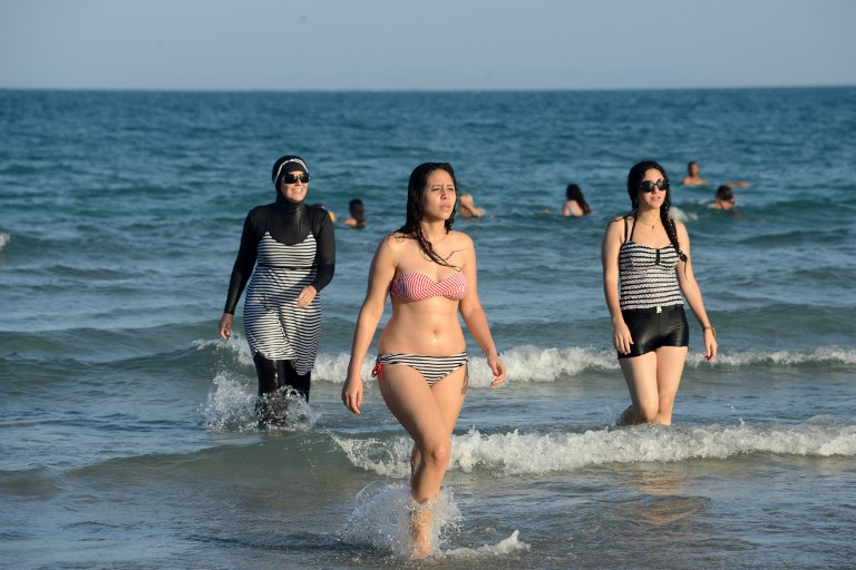 Women on beach with one, left, wearing a burkini, a full-body swimsuit designed for Muslim women. (AFP/FETHI BELAID)The debate launched this summer in France over the Burkini is not causing such a stir in North Africa where the Islamic swimsuit is uncontroversial as the dress-code on the beaches has become increasingly prudish. / AFP PHOTO / FETHI BELAID / TO GO WITH AFP STORY BY AMAL BELLALOUFI WITH AFP CORRESPONDENTS IN RABAT AND TUNIS