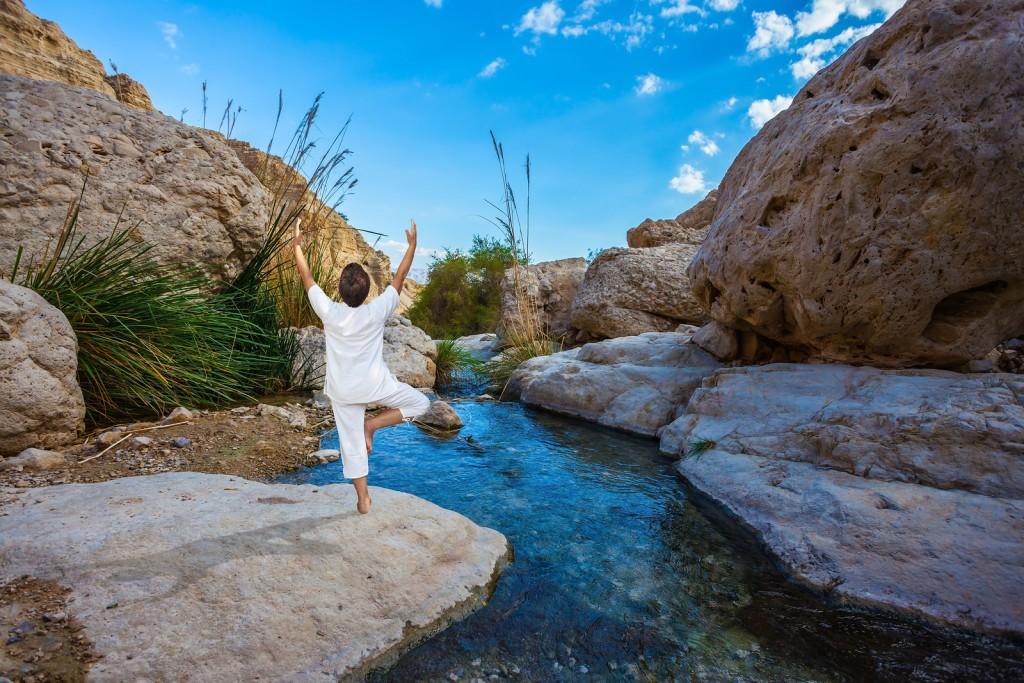 Elderly woman practices yoga on small lake in Ein Gedi