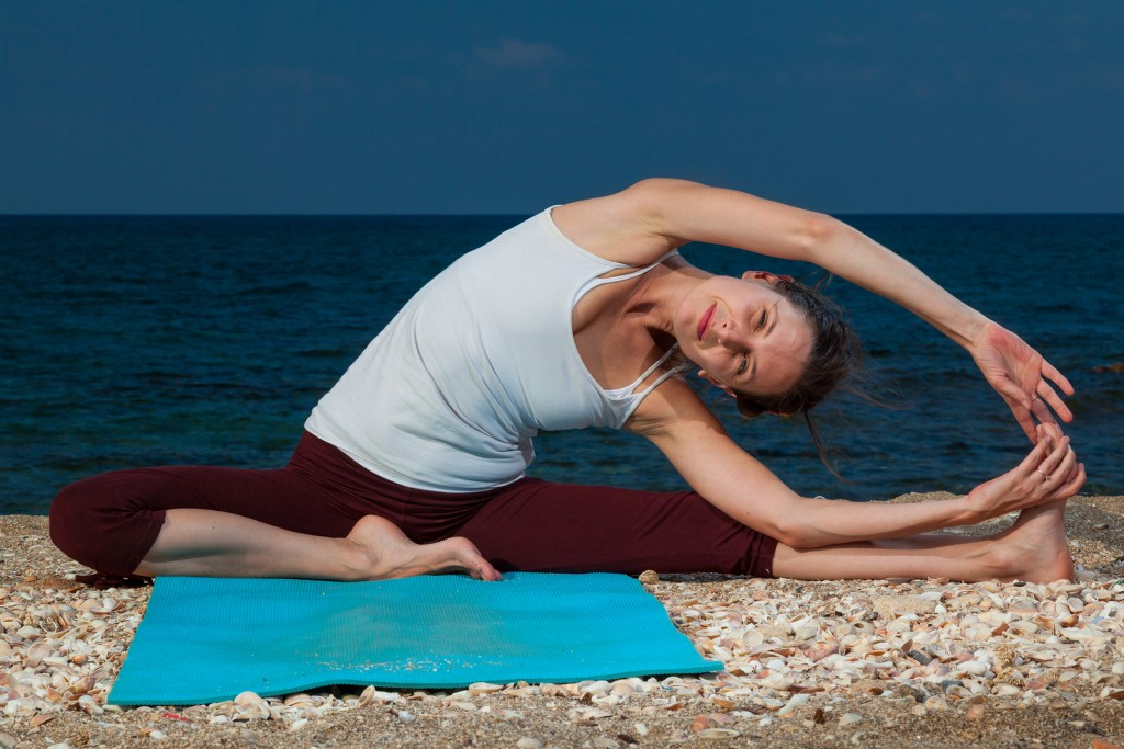 woman doing yoga on seacoast in haifa