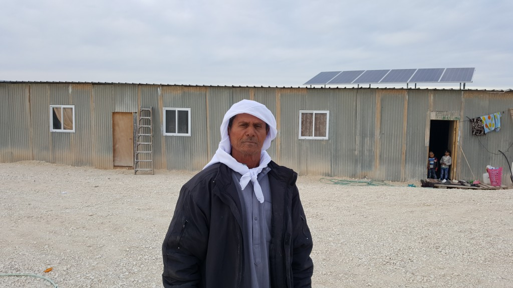 Ahmed Abu Al Qian in front of the tin shack he now calls home.