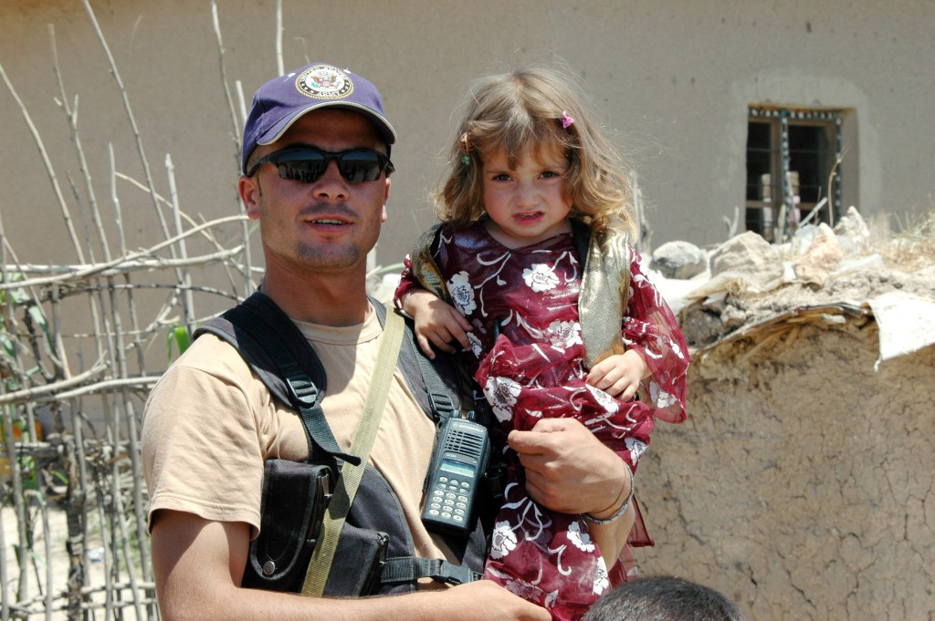 Portrait of a Kurdish Peshmerga fighter holding his daughter in their village outside of Dohuk, Iraq. (Public Domain)