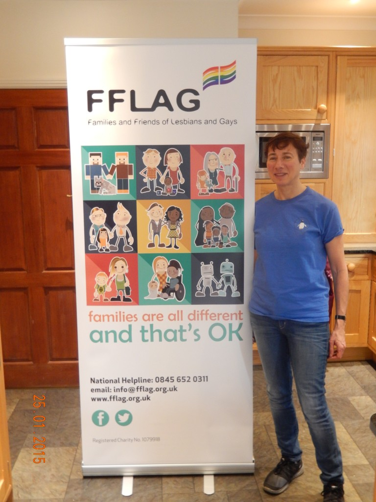 "Alison Walsh with the poster of FFLAG (Friends and Families of Lesbians and Gays) which is a national organisation and to which ""Parents of Jewish Gays and Lesbians"" is affiliated."