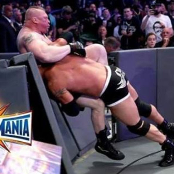 Goldberg spearing Lesnar right through the ringside barricade (Photo Credit: WWE.com)