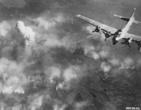A B-17 Flying Fortress flies over clouds and Polish countryside