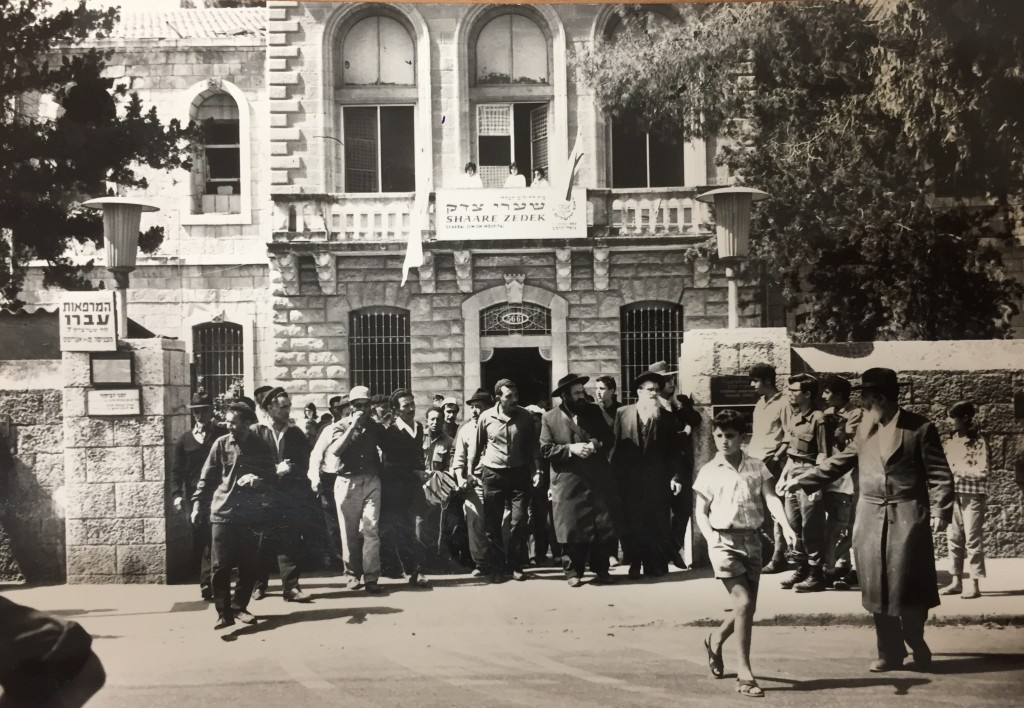 When the Six Day War ended an individual who passed away during the hostilities was accompanied to burial. Visible on the roof to the left of the front entrance is the point of impact of a Jordanian munition that struck Shaare Zedek but did not explode. — Photo: Shaare Zedek archive