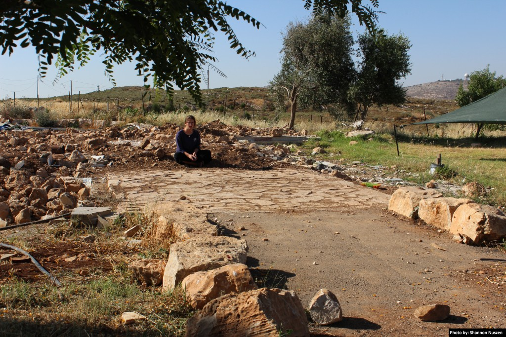 Amona teen sits at the front entrance to her home on the demolished hilltop.
