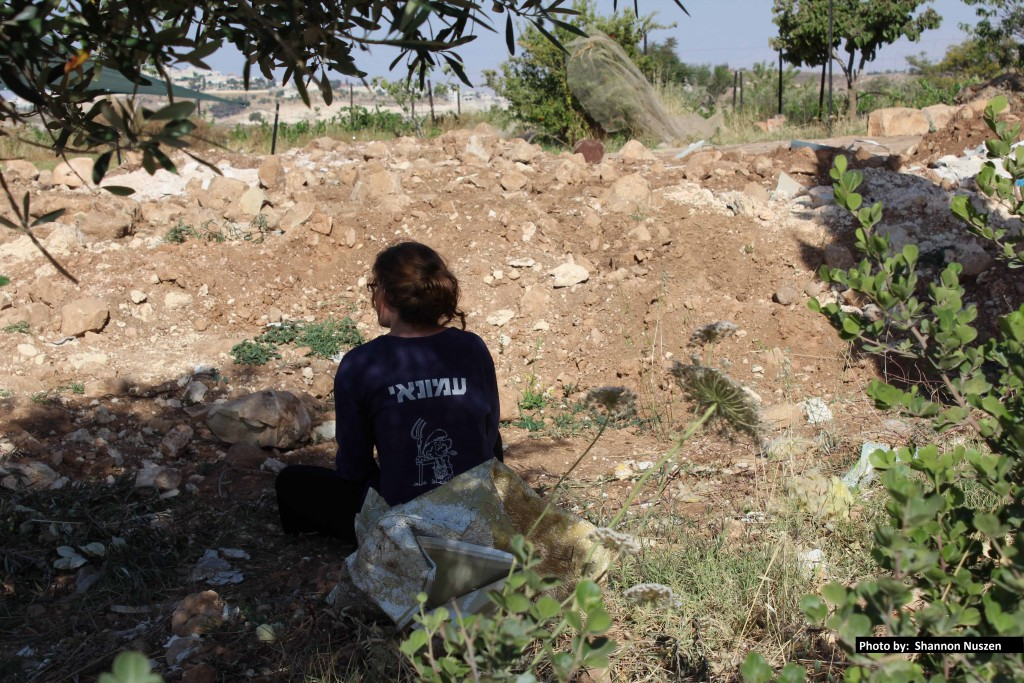 Tamar sits inside the ruins of her home, in the area where she says was her bedroom.