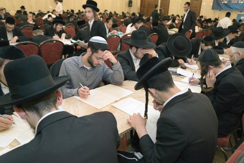 Dirshu members taking the Daf Hayomi B'Halacha test in the Belz Hall. (Dirshu)