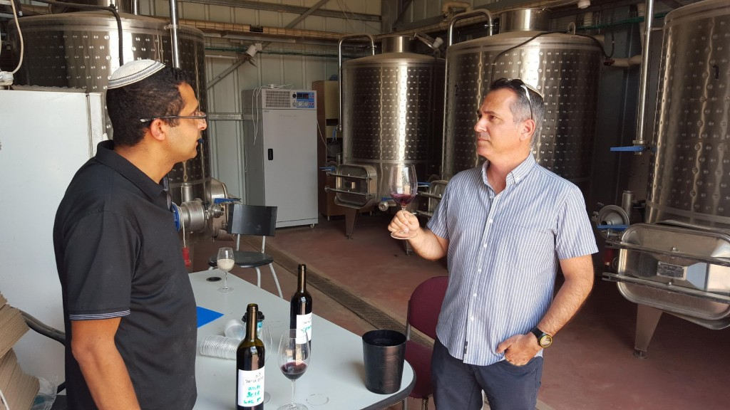 """Dr. Shivi Drori and a wine researcher discuss the properties of a sweet and strong """"sun wine"""" made from an indigenous grape varietal in Ariel. (courtesy)"""
