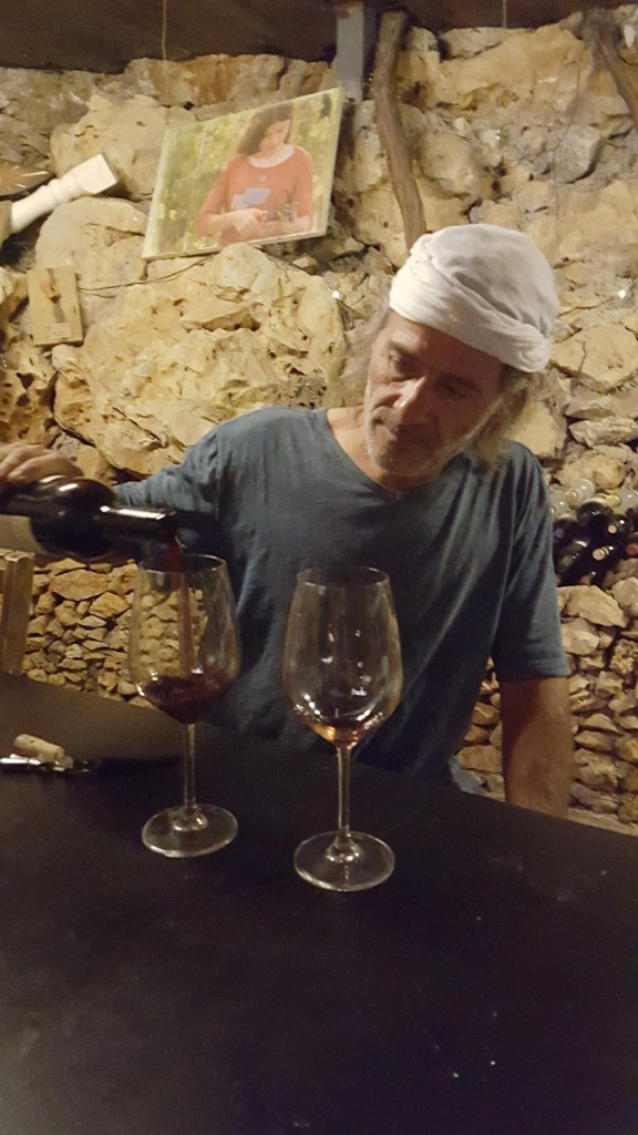 Yoram Cohen, owner of Tanya Winery in Ofra, pours a glass of wine in his backyard tasting room. (courtesy)