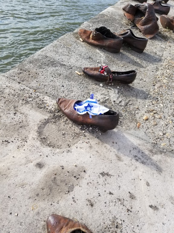 Israel flag someone had placed on a shoe at the Shoe Memorial on the Danube river bank .