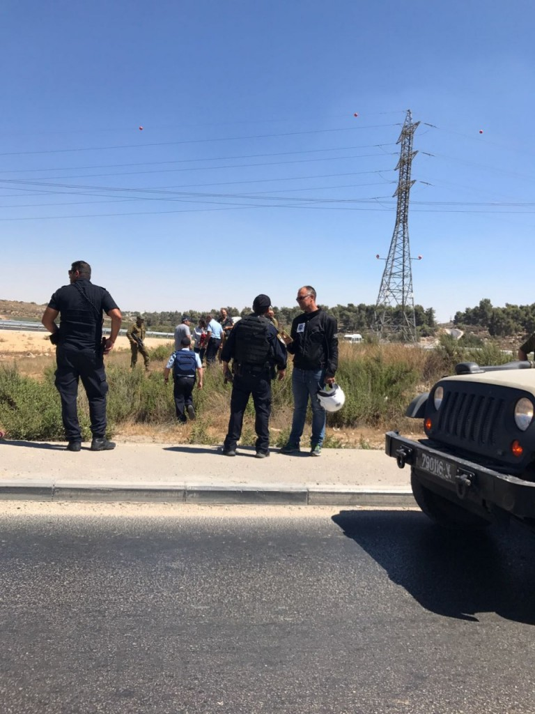 United Hatzalah EMT Shlomi Anavi speaking with security personnel at Gush Etzion junction on Wednesday after attempted terror attack was thwarted.
