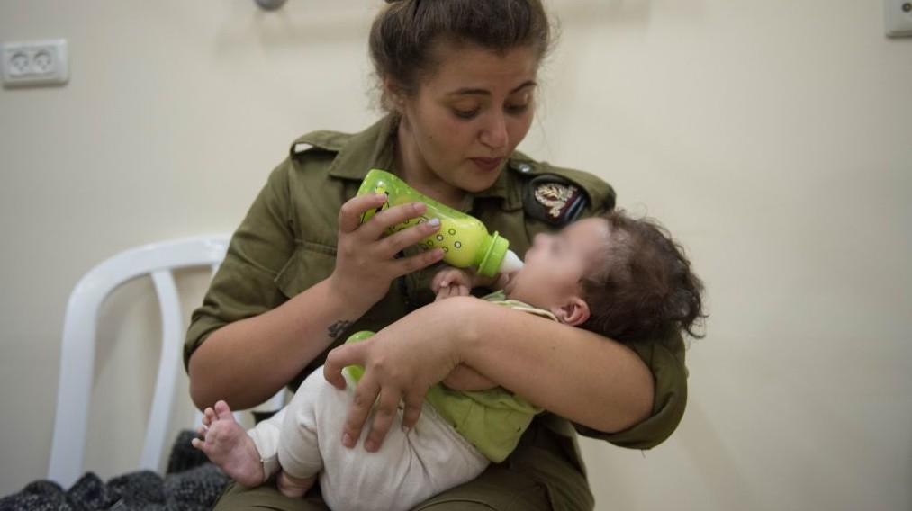 In an undated photo provided on July 19, 2017, an IDF soldier feeds a Syrian baby in Israel as part of Operation Good Neighbor. Photo courtesy of IDF Spokesman