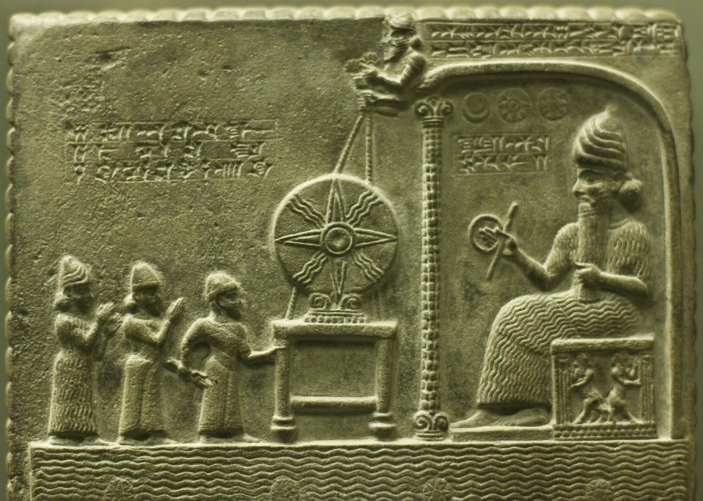 The god Shamash (right, seated) who holds a rod and ring, symbols that he measures out justice