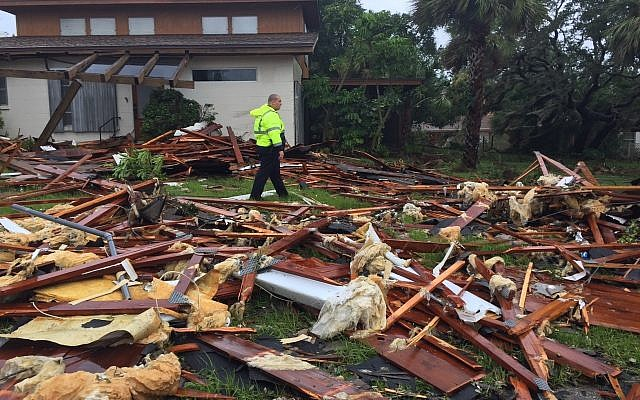 A Palm Bay police officer walks over debris from a two-story home in Brevard County, Florida, after Hurricane Irma passed over the state, Sunday, Sept. 10, 2017. (Red Huber/Orlando Sentinel via AP