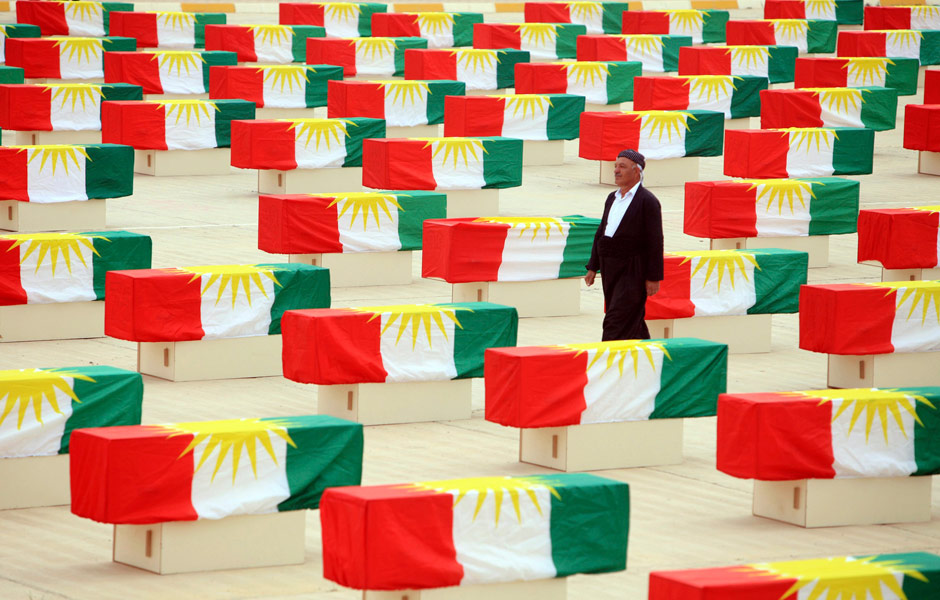 A Kurdish man walks between coffins draped with Kurdish flag containing the remains of victims during a burial ceremony in Sulaymaniyah, northeast of Baghdad, 28 May 2012. (Photo: Reuters - Stringer)