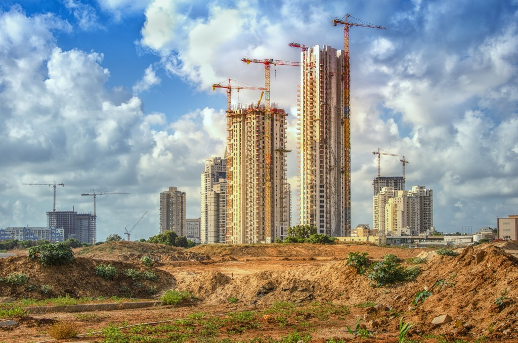 Bat Yam, Israel-May 27, 2016: View on part of the Sea Park huge real estate project. Some cranes work over new high-rise residential buildings on blue sky with perfect clouds background.