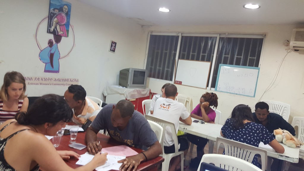 Volunteers help asylum seekers to fill out their Refugee Status Determination application forms in English and Hebrew