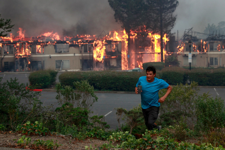 photo of A guest runs from a fire destroying the Hilton Wine Country Inn, Monday morning Oct. 9, 2017, in Santa Rosa, California.