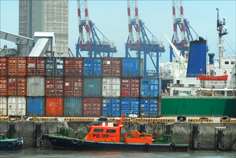 A tugboat passes containers waiting to be unloaded at the Taiwanese port of Kaohsiung. Photo: Larry Luxner