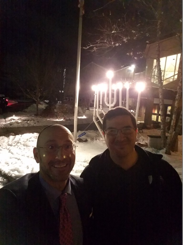 photo of Rabbi David Lerner and Scott Lerman in front of the giant Hanukkiah by the front entrance of Temple Emunah, Lexington, MA