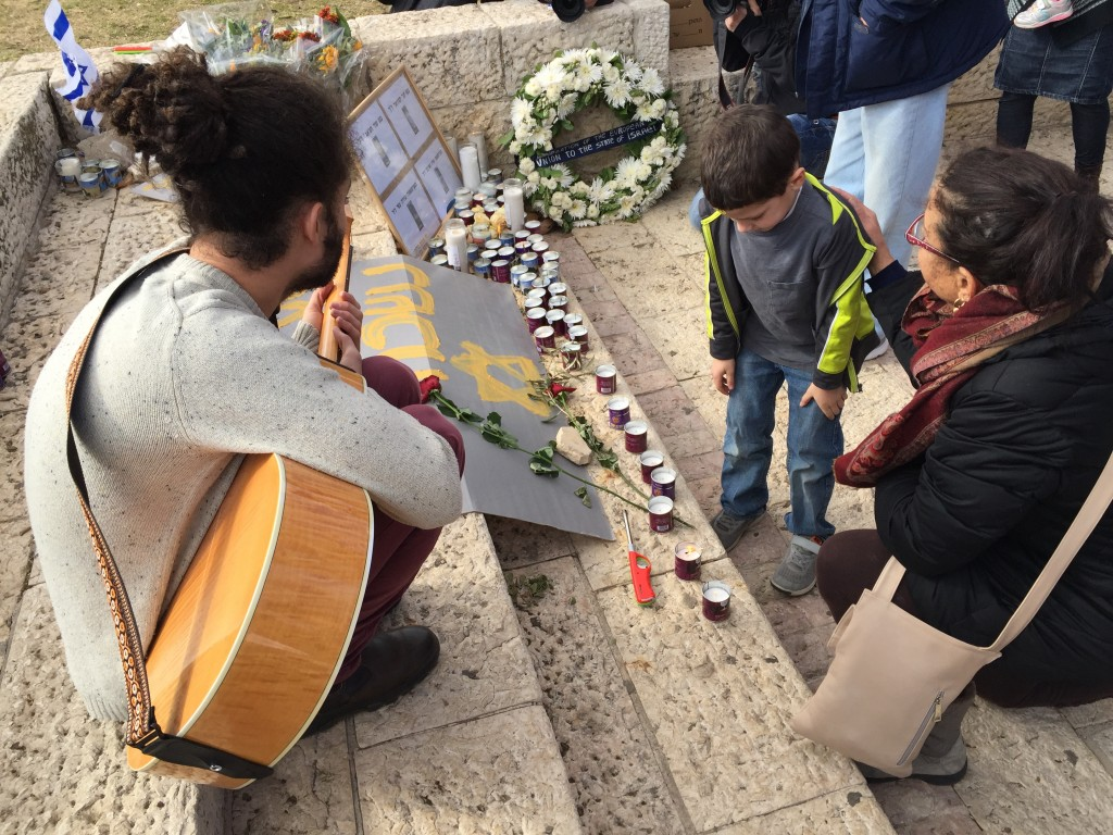 A child lights a memorial candle for the victims of the truck attack at the Hass Promenade (Shira Pasternak Be'eri)