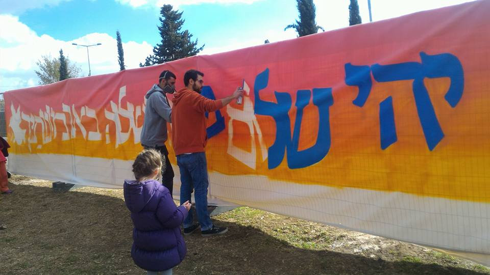 """Artists 4 Israel paint a mural imploring """"""""May there be peace with in your ramparts, tranquility in your citadels"""" (Psalms 122:7), which includes a Hebrew pun alluding to Armon Hanatziv, where the promenade is located. (Courtesy: Marsha Greengarten Solomon)"""