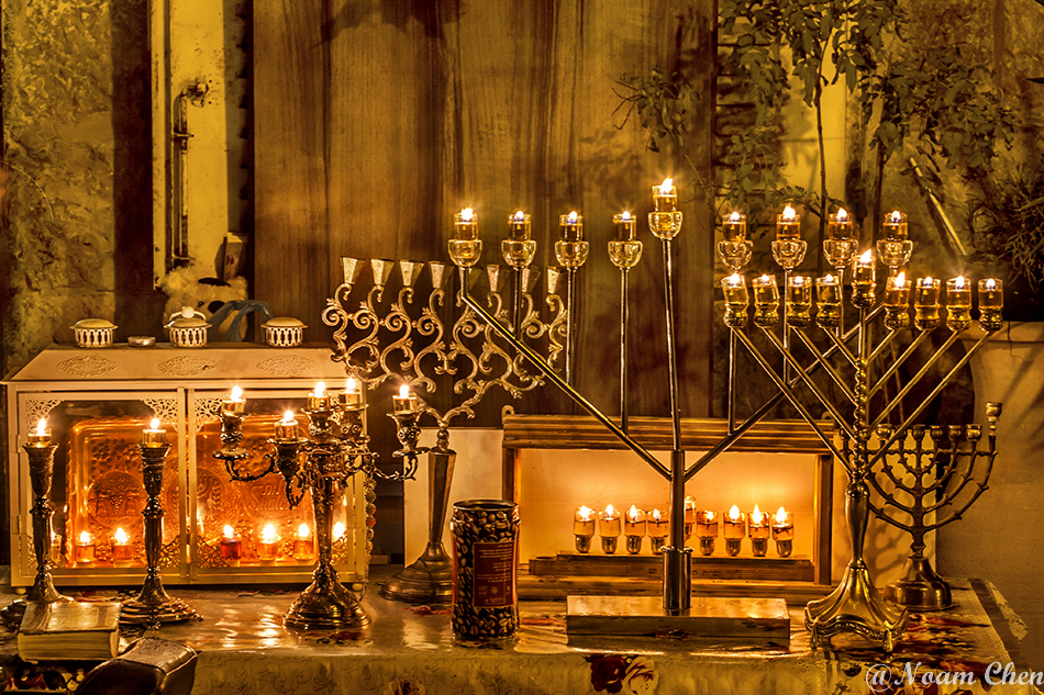 many menorahs lighted at night in a jerusalem neighborhood