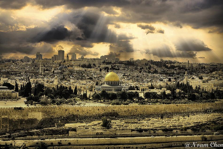 sun rays shining above the old city of jerusalem