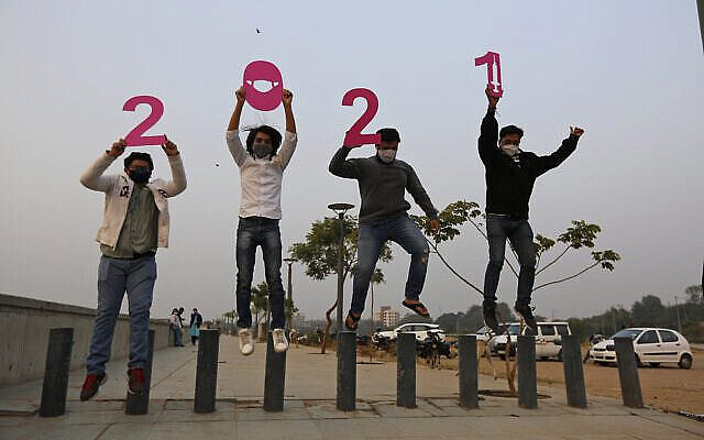 People hold cutouts to welcome the New Year in Ahmedabad, India, Thursday, Dec. 31, 2020. (AP Photo/Ajit Solanki)