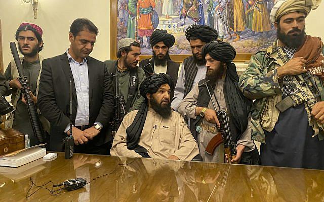 تصویر: رزمندگان طالبان پس از فرار «اشرف غنی» رئیس جمهور، کاخ ریاست جمهوری افغانستان در کابل را بتاریخ ۱۵ اوت ۲۰۲۱ تصرف کردند. مرد دوم، ایستاده از چپ، بادی گارد پیشین غنی است. (AP Photo/Zabi Karimi)